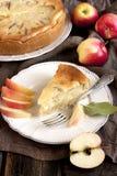 Neue Scheibe des Apfelkuchens mit ganzer Torte im Hintergrund Stockbild