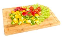 Neue Schnitte des Pfeffers und der Tomaten auf Weiß Lizenzfreies Stockfoto