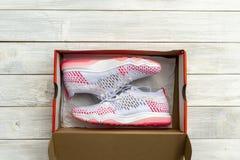 Neue Schuhe, in geboxt auf Holztischhintergrund stockfotografie