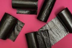Neue schwarze Abfalltaschen auf einem rosa Hintergrund stockbilder