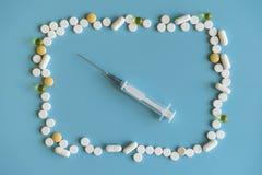Neue Spritze und Pillen und Kapsel auf blauem Hintergrund, Gesundheit und medizinischem Konzept, Drogenüberdosis Suringe und viel Lizenzfreie Stockfotos