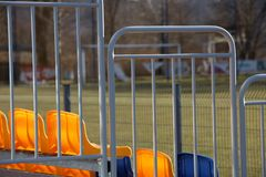 Neue Stände auf dem Fußballplatz des Metallhellen Baus mit Plastiksitzen in Blauem und in Gelbem Plätze für Fans im Stadion stockbild