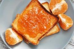 Neue Toast mit selbst gemachter Orangenmarmelade auf Gray Plate über hölzernem Hintergrund Stockbilder