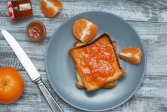 Neue Toast mit selbst gemachter Orangenmarmelade auf Gray Plate über hölzernem Hintergrund Lizenzfreies Stockfoto