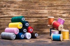 Neue verschiedene Farben des Threads im Satz und in einem Bündel alten Threads in der Nähe stockfotografie
