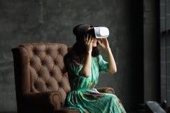 Neue Wirklichkeit ist hier hübsche junge Frau in VR-Kopfhörer, das VR-Kopfhörerdesign ist generisch und keine Logos, Frau mit Glä stockfotografie