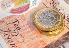 Neue zehn Pfund-Banknote und Münzen Stockbilder