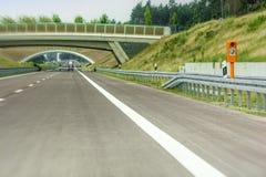 Neuer Abschnitt der Autobahn mit Notruf und grüner Brücke stockfotografie