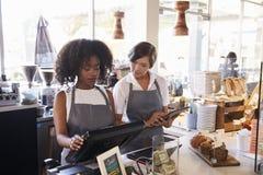 Neuer Angestellter empfängt Training an der Delikatessen-Prüfung stockbilder