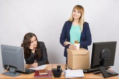 Neuer Angestellter im Büro hält glücklich nahen traurigen Kollegen der Sachen stockbilder