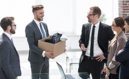 Neuer Angestellter mit dem persönlichen Eigentum, das im Büro steht lizenzfreie stockfotografie