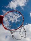 Neuer Basketballkorb schoss von unterhalb mit Wolken gegen blauen Himmel Lizenzfreie Stockfotos