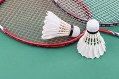 Neuer Federball des Badminton zwei mit Schlägern auf grünem Mattengericht Stockfoto