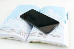 Neuer Flaggschiff Apples Iphone X Smartphone gesetzt auf Reisebuch Lizenzfreie Stockbilder