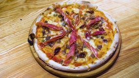 Neuer gebackener Pizzaschnitt in die Scheiben, die mit Schinkenscheiben, Frischkäse, vegatable Öl verzieren stock footage