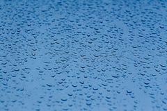 Neuer Hintergrund des Wassers fällt auf blaue Oberfläche Stockfotografie