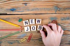 Neuer Job Hölzerne Buchstaben auf dem Schreibtisch Lizenzfreie Stockfotografie