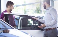 Neuer Käufer, der in ein Auto in einem Ausstellungsraum kommt Autohändlerstellung lizenzfreies stockbild