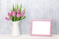 Neuer rosa Tulpenblumenstrauß und Fotorahmen Stockfotografie