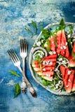 Neuer Sommer grillte Wassermelonensalat mit Feta, Arugula, Zwiebeln auf blauem Hintergrund Stockfoto