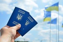 Neuer ukrainischer blauer biometrischer Pass mit Identifizierungschip an gegen blauen Himmel und wellenartig bewegenden Flaggenhi Stockfotos