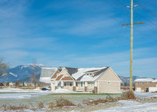 Neues Familienhaus mit Bergblick und Vorgarten im Schnee am sonnigen Tag des Winters Lizenzfreies Stockfoto