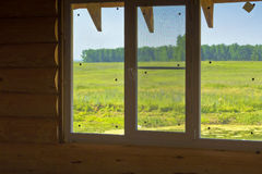 Neues Fenster im hölzernen Blockhaus, welches die Wiese und den Wald übersieht Lizenzfreies Stockbild