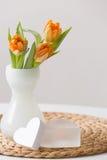 Neues Frühlingsbündel orange Tulpen in einem netten weißen Glasvase und zwei nette Herzsymbole auf dem Strohbrett Wenig Tabelle v Lizenzfreie Stockbilder