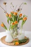 Neues Frühlingsbündel orange Tulpen und Grünblätter und kleine Vögel in den netten cristal Glasvasen auf dem Strohbrett und Stockbilder