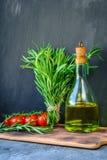Neues Gartenbündel Rosmarin, Tomaten mit einer Flasche Rosmarinöl oder Olivenöl auf Schneidebrett über Steinhintergrund Stockfotos