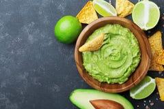 Neues Guacamolebad mit Avocado, Kalk und Nachos auf schwarzer Tischplatteansicht Kopieren Sie Platz Traditionelles mexikanisches  lizenzfreie stockfotos