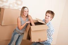 Neues Haus: Beweglicher Kasten der jungen Paare, entpackend lizenzfreie stockbilder
