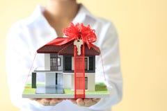 Neues Haus des Geschenks und Immobilienkonzept, weibliche Mannhände, die Musterhaus mit rotem Band und das Auto mit Schlüsseln ha stockfotografie
