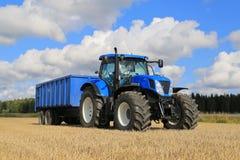 Neues Holland T7 250 Traktor und Ackerwagen auf Feld Lizenzfreie Stockfotos
