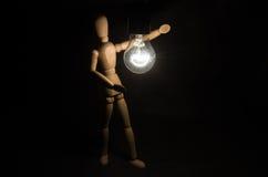 Neues Ideenkonzept Hölzerne Zahl des Mannes und helle elektrische Birne Stockfoto