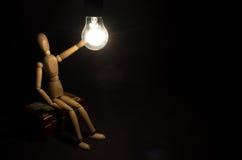 Neues Ideenkonzept Hölzerne Zahl des Mannes und helle elektrische Birne Lizenzfreies Stockfoto
