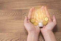 Neues Ideenkonzept, junge Frauen übergeben das Halten der Glühlampe und der Münzen auf hölzernen Hintergründen und neuer Ideenkon lizenzfreies stockfoto