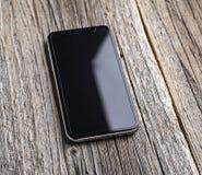 Neues iPhone X 10 auf einem hölzernen Hintergrund, Atelieraufnahme Lizenzfreie Stockfotografie