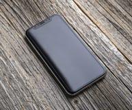 Neues iPhone X 10 auf einem hölzernen Hintergrund, Atelieraufnahme Lizenzfreies Stockbild