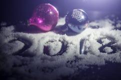Neues 2018-jähriges des Hintergrundes mit Zahlen, Tanne, Bälle im Schnee Dunkelheitshintergrund des selektiven Fokus Lizenzfreie Stockbilder