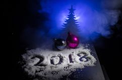 Neues 2018-jähriges des Hintergrundes mit Zahlen, Tanne, Bälle im Schnee Dunkelheitshintergrund des selektiven Fokus Lizenzfreies Stockbild