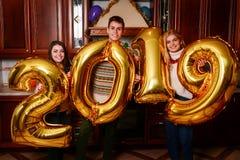 Neues 2019-jähriges kommt Gruppe des netten Tragens der jungen Leute lizenzfreies stockfoto