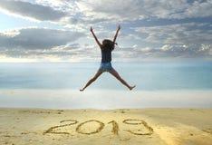 Neues Jahr 2019 auf dem Sand, glückliches Mädchen mit den Händen, die oben auf den Strand springen Stockfoto