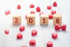2018 neues Jahr auf hölzernem Würfel mit Gruppe mini rotem Herzen auf Weiß Stockbilder