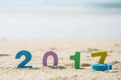 Neues Jahr 2017, bunter Text auf dem Strandsand Stockbild