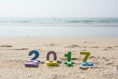 Neues Jahr 2017, bunter Text auf dem Strandsand Lizenzfreie Stockfotos