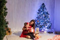 Neues Jahr des Mutter-und kleiner Junge offenes Geschenk-Weihnachtsbaums lizenzfreies stockfoto