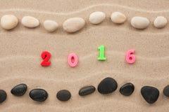 Neues Jahr 2016 geschrieben auf den Sand unter Steinen Stockbilder