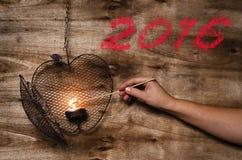 Neues Jahr 2016 geschrieben durch Feuerbürste auf hölzernen Hintergrund Beleuchten des Herzens Lizenzfreies Stockbild