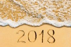 Neues Jahr 2018 handgeschrieben auf dem sandigen Strand Lizenzfreie Stockfotografie